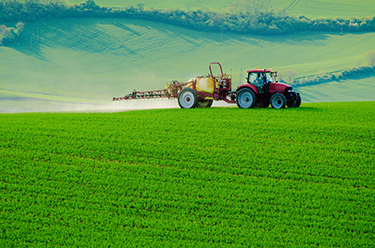 Tractor applying chemicals to green field